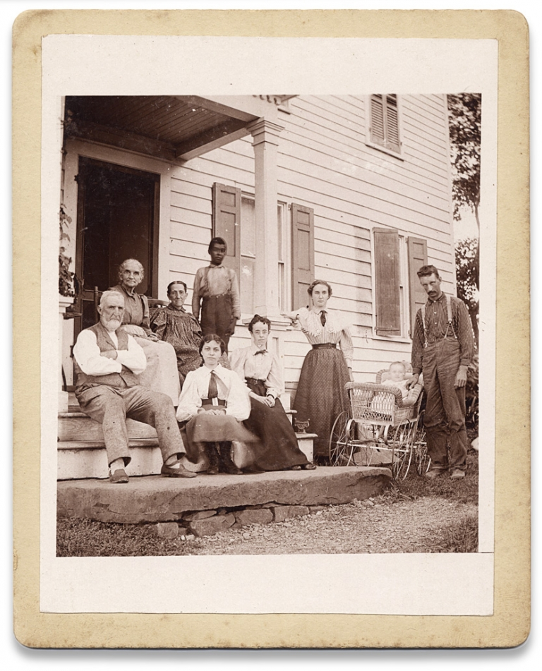 [Vernacular Photograph of a White Family on a Porch with an African American Boy]. Unkwn.
